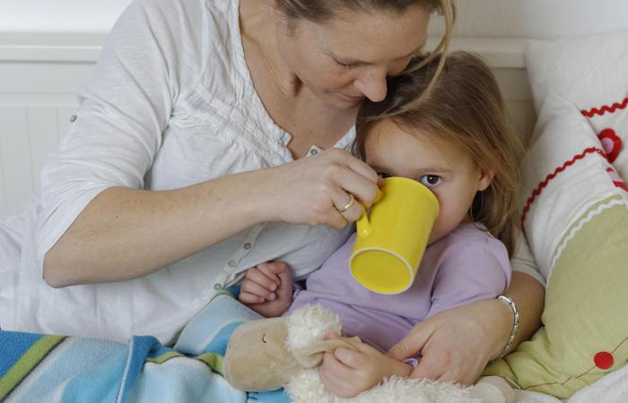Bolesna devojčica pije čaj